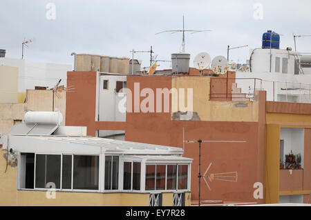 Antennas on a Roof over a Cloudy Sky - Stock Photo