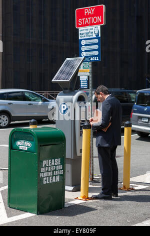 A man pays for parking at a solar powered multi-space pay station at a municipal parking lot in White Plains, New - Stock Photo