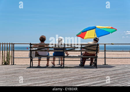 Three Elderly People (Two Women, One Man) Sitting on a Bench.  Man is under an umbrella and seemingly taking a nap.