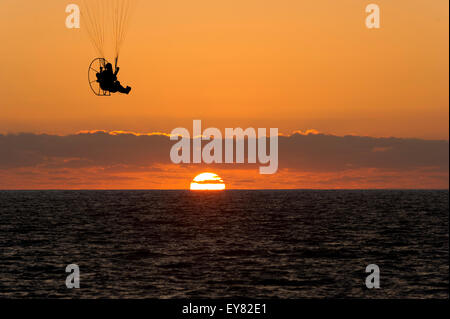 Paraglider with detailed chute lines is silhouetted against an orange sky cloudscape with the sun setting on the - Stock Photo