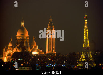 Sacre-Coeur and Eiffel Tower above Paris skyline at night - Stock Photo