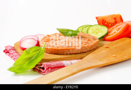 Raw burger patty and sliced vegetables on cutting board - Stock Photo