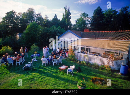 Friends sharing food, coffee and conversation at summer house on Tranholmen island in Stockholm Archipealgo in Baltic - Stock Photo