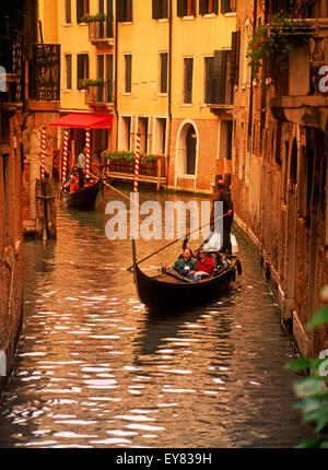 Gondolas filled with tourists passing on narrow canals in Venice - Stock Photo
