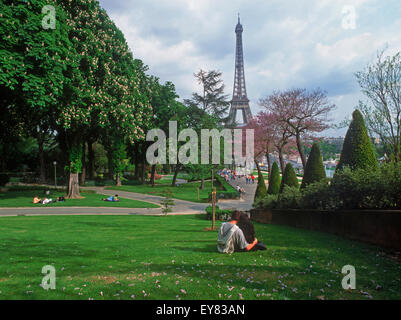 Couple sitting on lawn in Trocadero near Palais de Chaillot in Paris with Eiffel Tower - Stock Photo