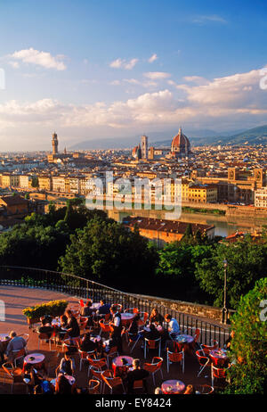 People and tables at outdoor cafe at (Plaza) Piazzale Michelangelo above Arno River and Florence near sunset - Stock Photo
