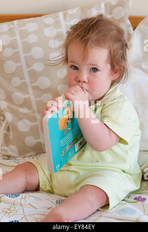 Baby girl sitting on the bed biting on her book - Stock Photo