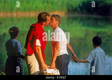 Family of four on picnic near countryside pond in Bavaria, Germany Mother and father kissing - Stock Photo