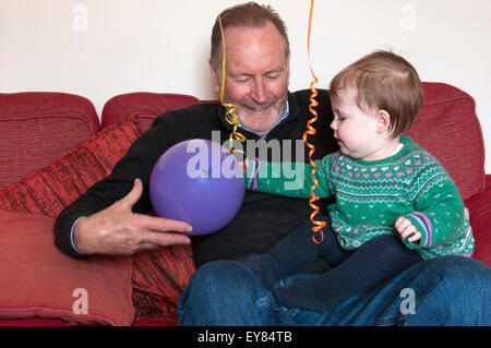 Baby girl sitting on her grandfathers lap playing with a balloon - Stock Photo