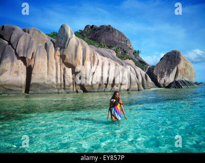 Native woman with colorful sarong walking in aqua waters at Anse Source d Argent on La Digue in Seychelles - Stock Photo