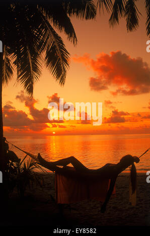Woman in hammock between palm trees on tropical island holiday at sunset - Stock Photo
