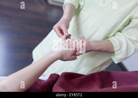Young woman receiving Shiatsu treatment - Stock Photo