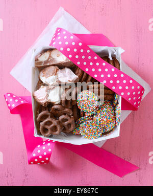 Chocolate candy and cookies gift box, with chocolate covered marshmallows, pretzels, candy and cookies on vintage - Stock Photo