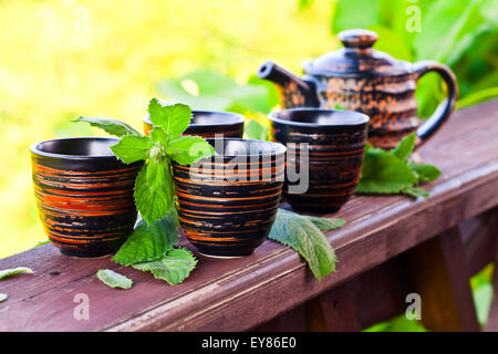 small cups with peppermint tea in garden - Stock Photo
