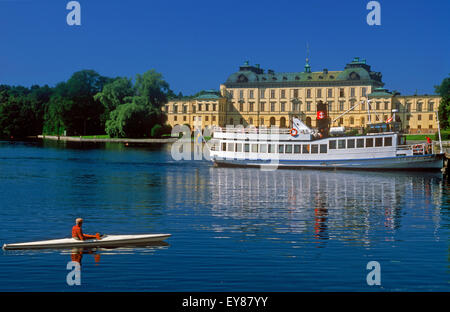 Ferryboat and kayak resting on calm water in front of the Royal residence at Drottningholm Palace near Stockholm - Stock Photo