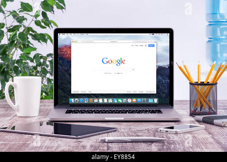 Varna, Bulgaria - May 29, 2015: Open Apple MacBook Pro Retina which shows Google search web page with ipad and iphone - Stock Photo