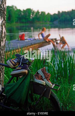 Two girls enjoying summer swim from lakeside dock  in Sweden - Stock Photo