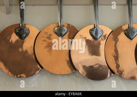 Copper pans hanging in the kitchen of Hardwick Hall, Derbyshire, England, UK - Stock Photo