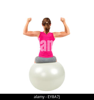 Sporty woman sitting on a gymnastic-ball and doing workout - Stock Photo