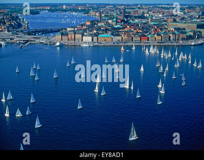 Aerial view of sailboats surrounding The Old Town of Stockholm during summer regatta on Saltsjön waters a bay of - Stock Photo