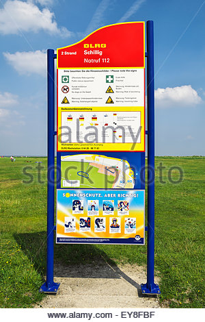 A DLRG (German Lifesaving Assn.) sign at Schillig, Germany, warns of dangers, displays other information in English - Stock Photo
