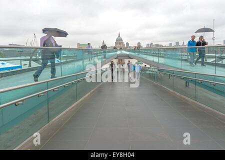 Pedestrians crossing Millennium Bridge, a suspension footbridge across River Thames, Bankside, London, England, - Stock Photo