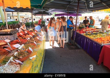 People browsing olives stall and fruit and veg stall in a french market - Stock Photo