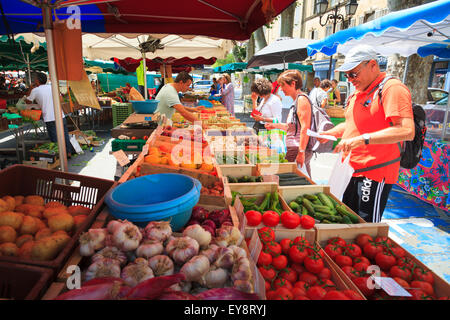 Customers buying produce from a fruit and veg French market stall - Stock Photo