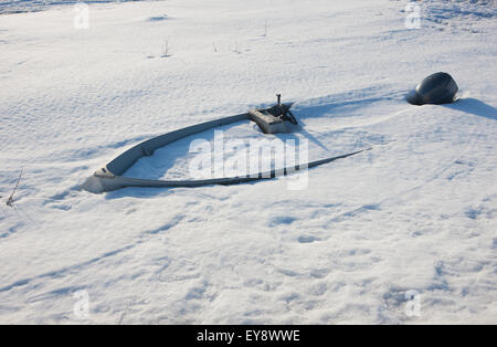 Boat with an outboard engine buried in snow; Noatak, Alaska, United States of America - Stock Photo