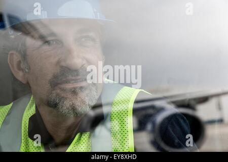 Portrait of airport worker looking out of window at airplane - Stock Photo