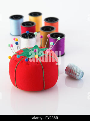 Tomato pin cushion and spools of thread - Stock Photo