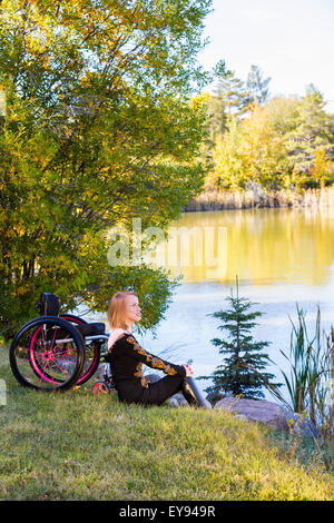 Young disabled woman sitting beside her wheelchair in a city park in autumn; Edmonton, Alberta, Canada - Stock Photo