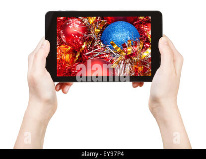 take photo of red Christmas decorations with tablet pc isolated on white background - Stock Photo