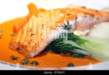 Close up of fresh baked salmon in sauce - Stock Photo
