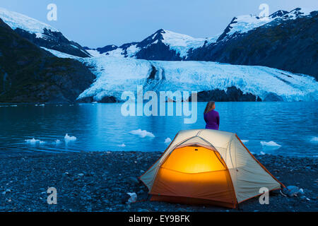 Female Camper Enjoying The View Of Portage Glacier At Dusk With A Lit Tent In The Foreground, Chugach National Forest, - Stock Photo