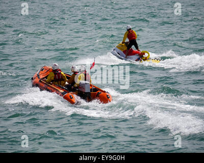 RNLI Lifeguards riding a Rib and a jetski in the sea - Stock Photo