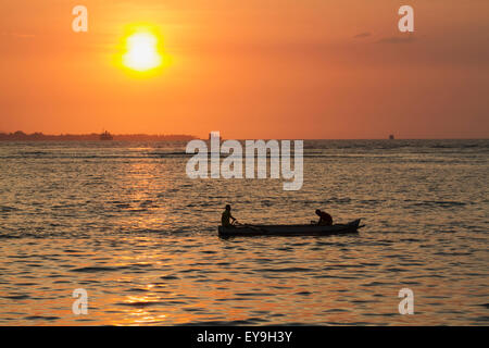 Men in a boat at sunset; Dili, East Timor - Stock Photo