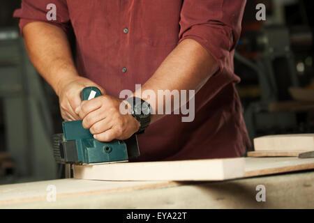 Carpenter working with electric planer on wooden plank in workshop. - Stock Photo