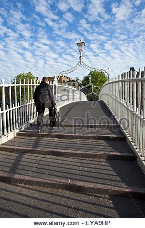 Dublin, Ireland; A Man In A Suit On The Ha'penny Bridge Crossing The River Liffey - Stock Photo