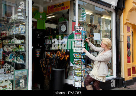 Woman Looking At Postcards Outside Gift Shop; Killarney, County Kerry, Ireland - Stock Photo