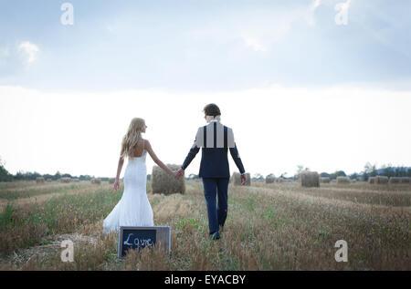 "Married couple taking a walk on a field of hay bales, leaving back a mini blackboard that is written the word ""love"". - Stock Photo"