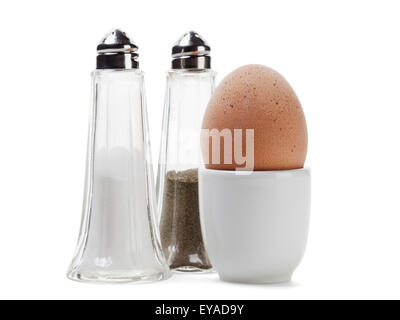whole brown egg in eggcup with salt and pepper shakers, isolated with clipping path - Stock Photo