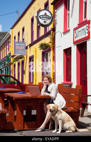A Woman Sits At An Outdoor Table Working On Her Laptop Computer With Her Dog Sitting Next To Her; Allihies, County - Stock Photo