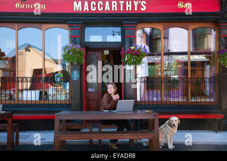 A Woman Sits At An Outdoor Seating Area Outside A Bar With Her Dog And Laptop Computer; Castletownbere, County Cork, - Stock Photo