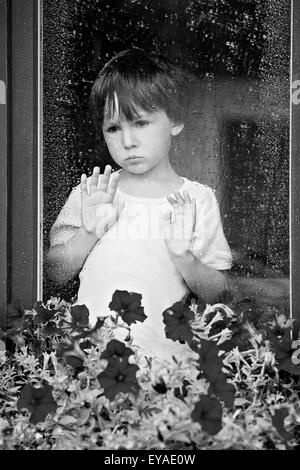 Little boy behind the window in the rain, looking sad - Stock Photo
