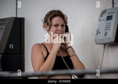 A woman uses a public telephone in Mariel near Havana, Cuba, 17 July 2015. PHOTO: MICHAEL KAPPELER/DPA - Stock Photo
