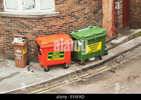 Bins For Waste And Recycling Lined Up Against A Brick Building; Limerick, County Limerick, Ireland - Stock Photo