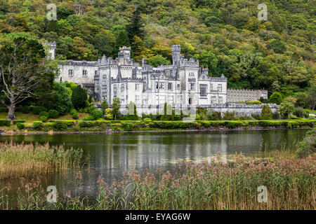 Stone castle reflecting in lake with treed hillside; County Galway, Ireland - Stock Photo
