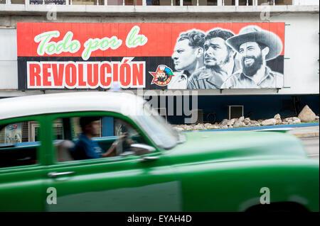 HAVANA, CUBA - JUNE 12, 2011: Vintage American car passes in front of billboard promoting Communist propaganda on - Stock Photo