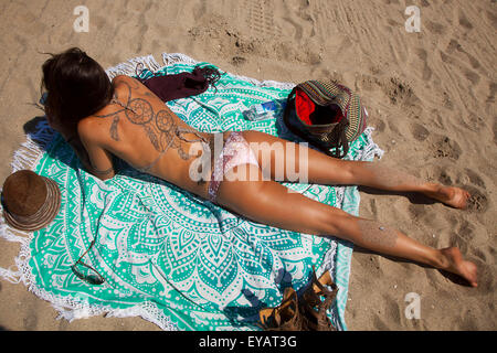 Sunbather with tattoes, Venice Beach, California - Stock Photo